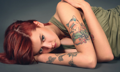 bigstock-Young-tattooed-girl-on-dark-ba-55541027