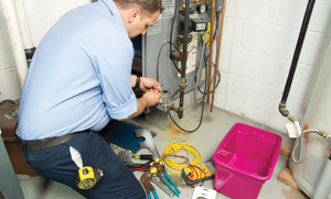 bigstock-Plumber-fixing-gas-furnace-40351003